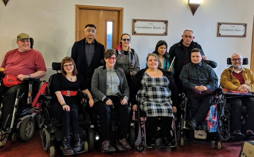 Photograph of Esther and 9 of her supporters (6 using wheelchairs, one with a symbol cane and two wearing coloured lenses) outside the courtroom.